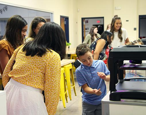 Student showing 3D printer to guests