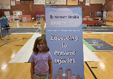 Child in mask in front of Banner Safety Town sign