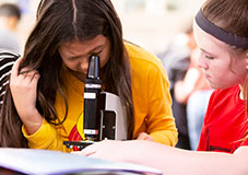 two students looking at microscope in classroom lab